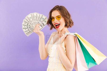 Photo pour Portrait d'une jeune femme ludique en lunettes de soleil tenant des sacs à provisions et des billets de banque sur fond violet - image libre de droit