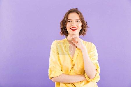 Foto de Retrato de una joven alegre vestida con ropa de verano mirando a la cámara sobre fondo violeta - Imagen libre de derechos