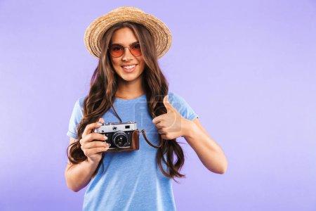 Photo pour Portrait d'une jeune fille heureuse en chapeau et lunettes de soleil isolées sur fond violet, tenant un appareil photo vintage, montrant les pouces vers le haut - image libre de droit