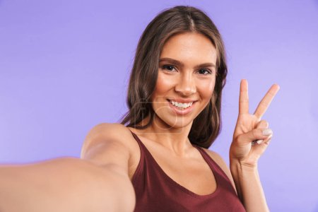 Portrait of a cheerful young girl taking a selfie isolated over violet background, holding mobile phone, showing peace