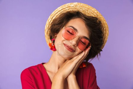 Photo for Pleased Pretty brunette woman in dress, straw hat and sunglasses posing with closed eyes while holding arms near her cheek over purple background - Royalty Free Image