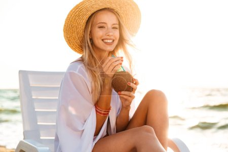 Image of lovely smiling woman 20s in straw hat drinking exotic cocktail while sunbathing in deck chair on beach during summer sunrise