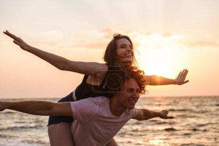 Photo pour Portrait d'un charmant jeune couple à la plage, s'amusant, balade à dos de cochon - image libre de droit