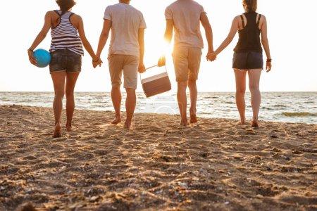 Photo pour Recadrée photo vue arrière du groupe d'amis épris de couples marchant en plein air sur la plage s'amuser boîtes avec nourriture et boissons. - image libre de droit