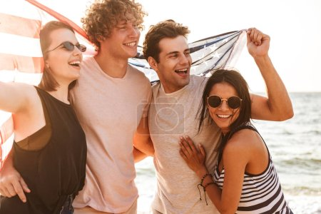 Photo for Image of happy group of friends outdoors on the beach holding USA flag having fun. - Royalty Free Image