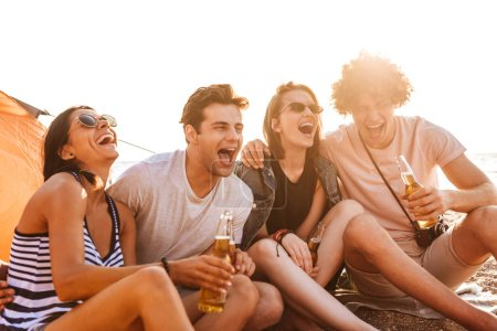 Photo for Group of laughing young friends having fun time together at the beach, drinking beer, camping - Royalty Free Image
