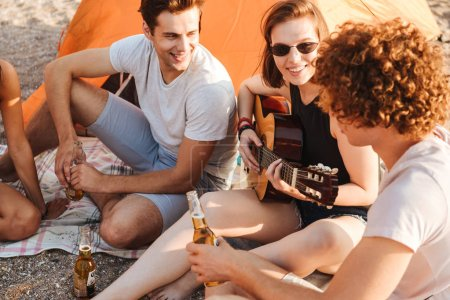 Group of joyful young friends having fun time together at the beach, drinking beer, playing guitar while camping