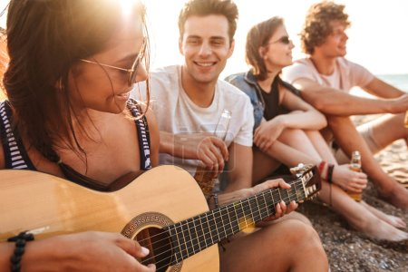 Group of happy young friends having fun time together at the beach, drinking beer, playing guitar while camping