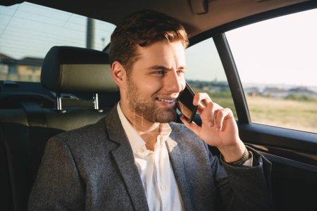 Photo pour Portrait d'un homme de succès directeur en costume parler sur smartphone tout en arrière assis dans la voiture de classe affaires - image libre de droit