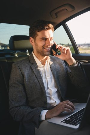 Photo pour Image d'homme directeur réussie en costume parler sur smartphone et travaillant sur ordinateur portable tout en arrière assis dans la voiture de classe affaires - image libre de droit