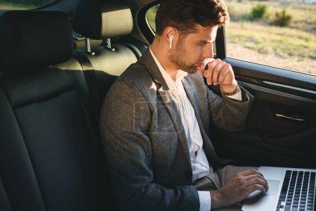 Photo pour Photo d'un homme réussi portant costume et bluetooth écouteurs travaillant sur ordinateur portable tout en arrière assis dans la voiture de classe affaires - image libre de droit