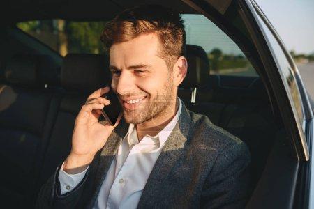Photo pour Portrait d'homme réussi de 30 ans en costume classique, parler sur smartphone en arrière assis dans la voiture de classe affaires - image libre de droit