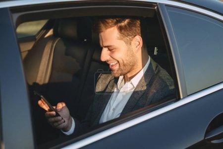 Photo pour Photo de l'heureux homme en costume classique, maintenez et avec téléphone portable retour assis dans la voiture de classe affaires - image libre de droit
