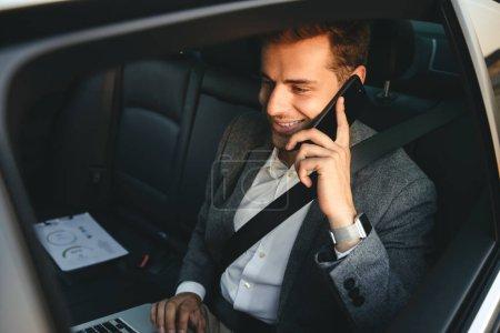 Photo pour Image d'homme jeune réalisateur en costume parler sur smartphone et travaillant sur ordinateur portable dos assis dans la voiture de classe affaires avec ceinture de sécurité - image libre de droit