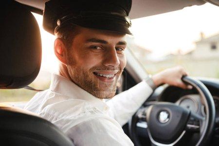 Photo pour Portrait d'un beau chauffeur de taxi caucasien portant uniforme et casquette souriant et vous regardant en conduisant une voiture - image libre de droit