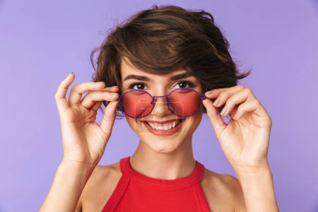 Photo for Image of cheerful woman 20s in casual wear and sunglasses looking at you with smile isolated over violet background - Royalty Free Image