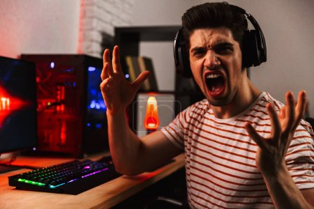 Side view of Screaming gamer playing video games on computer while gesturing and looking at the camera at home