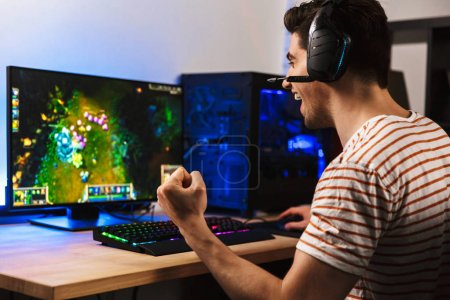Photo for Portrait of delighted young guy playing video games on computer wearing headphones and using backlit colorful keyboard - Royalty Free Image