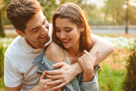 Image of happy young loving couple walking outdoors while hugging.