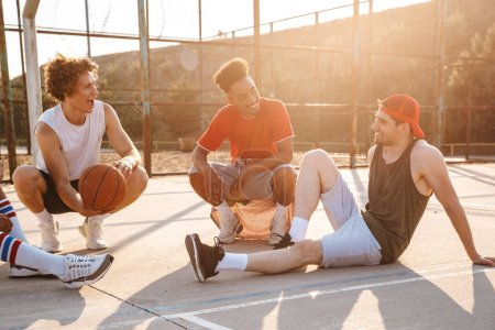 Group of cheerful multiethnic friends basketball players sitting at the sports ground