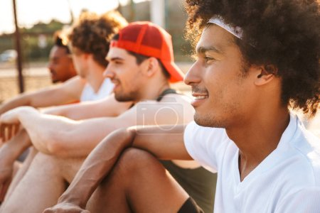 Image of handsome men players sitting at basketball playground outdoor and watching game during summer sunny day