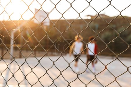 Group of young cheerful multiethnic men basketball players playing basketball at the sport ground, focus on fence