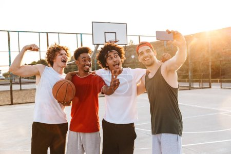 Strong multiethnic men smiling and taking selfie on smartphone while playing basketball at playground outdoor during summer sunny day