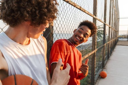 Two young smiling multiethnic men basketball players standing at the sport ground, talking