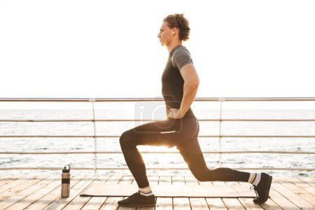 Portrait of a healthy sportsman doing lunges exercises on a fitness mat the beach, listening to music with earphones