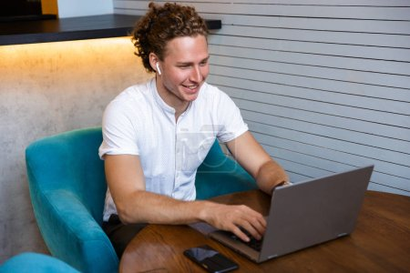 Photo for Smiling curly business man using laptop computer while sitting by the table in cafe - Royalty Free Image