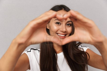Photo of excited cheerful young woman isolated over grey background showing heart love gesture.
