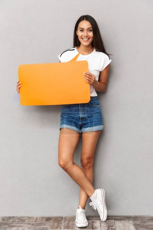 Beautiful woman wearing casual clothing holding blank announcement with copyspace isolated over gray background