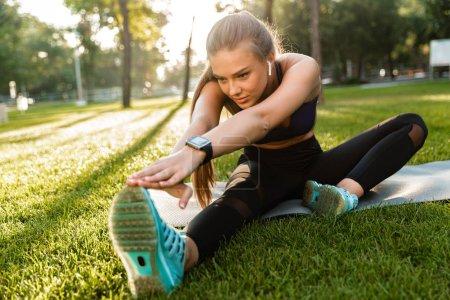 Photo pour Photo de la jeune femme sportive incroyable dans le parc en plein air faire des exercices d'étirement sportif . - image libre de droit