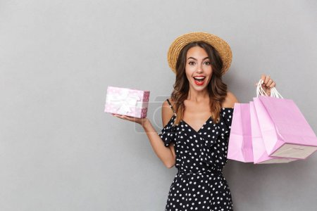 Photo for Portrait of a laughing young girl in dress and straw hat over gray background, holding present box and shopping bags - Royalty Free Image
