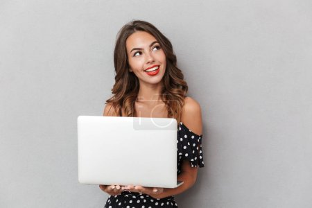 Photo for Portrait of a smiling young girl in dress over gray background, holding laptop computer - Royalty Free Image
