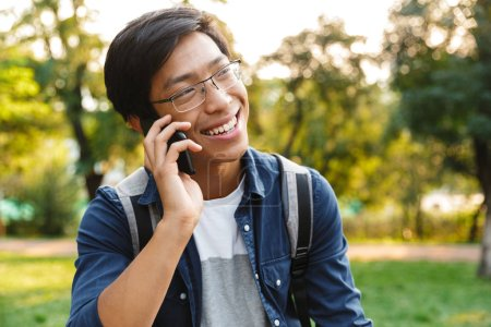 Photo for Smiling asian male student in eyeglasses talking by smartphone and looking away while being in park - Royalty Free Image