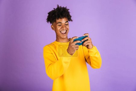 Photo for Portrait of a smiling young afro american man dressed in hoodie isolated, playing games on mobile phone - Royalty Free Image