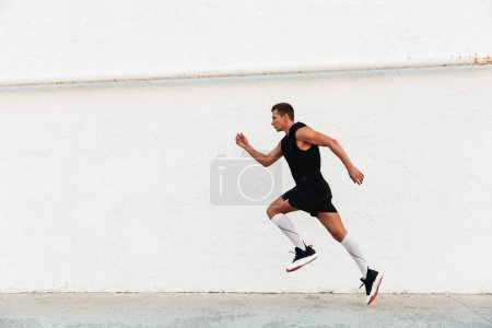 Photo for Image of handsome strong young sportsman running outdoors. - Royalty Free Image