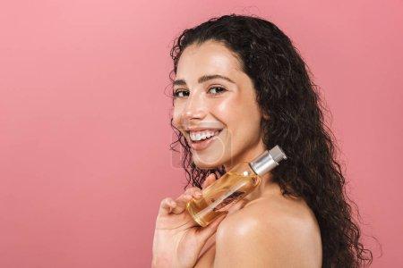 Photo pour Portrait de jolie joyeuse belle jeune femme posant isolée sur fond rose prendre soin de sa peau tenant l'huile . - image libre de droit