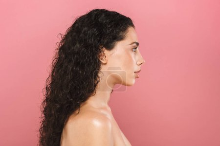 Photo for Portrait of amazing beautiful young woman with healthy skin posing isolated over pink background looking aside. - Royalty Free Image