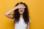 Image of pretty woman 20s with curly hair smiling and covering eyes with palm isolated over yellow background