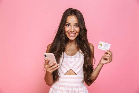 Photo pour Photo de belle femme 20s portant robe tenant téléphone portable et carte de crédit isolé sur fond rose - image libre de droit