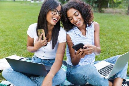 Photo pour Deux souriant étudiants jeunes filles assis sur l'herbe au campus, étudiant, tenant des téléphones mobiles - image libre de droit