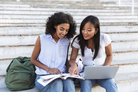 Two cheerful young girls students sitting on steps at the campus, studying with laptop computer and textbooks