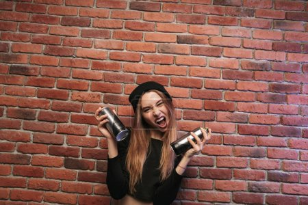 Photo for Image of subcultural hip hop girl 20s standing against brick wall with spray cans - Royalty Free Image