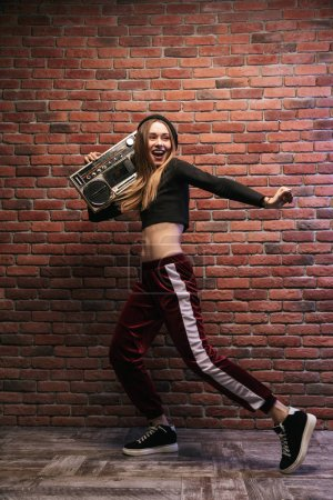 Photo for Full length image of subcultural woman 20s standing against brick wall and holding boombox - Royalty Free Image