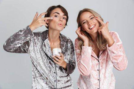Photo pour Deux filles gaies portant un pyjama debout isolé sur fond gris, appliquant une lotion visage - image libre de droit