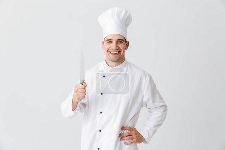 Photo pour Chef cuisinier heureux portant uniforme tenant un couteau isolé sur fond blanc - image libre de droit