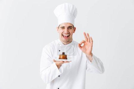 Photo pour Homme joyeux chef cuisinier portant uniforme montrant pâtisserie sur une plaque isolée sur fond blanc - image libre de droit