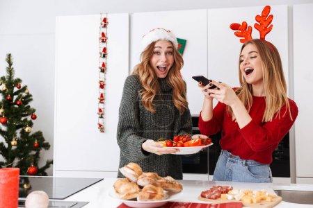 Photo pour Image de femmes joyeuses 20s riant tout en célébrant le Nouvel An dans l'appartement - image libre de droit